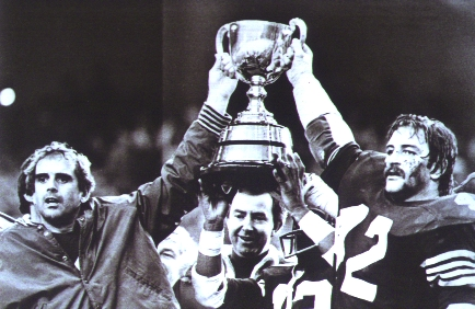 Prime Minister Joe Clark (centre) hands 1979 Grey Cup to Eskimos' QB Tom Wilkinson (left) and linebacker Dan Kepley